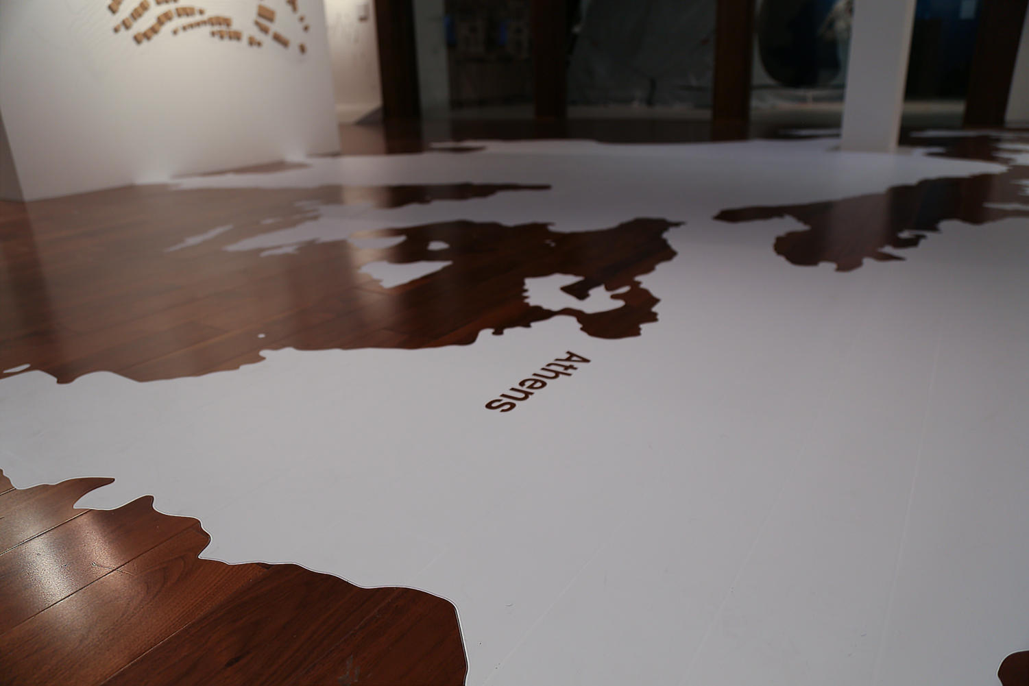 A+map+of+Greece+has+been+painted+on+the+wooden+floor+of+the+exhibition+to+help+visitors+experience+the+heart+of+the+camp.+%0A
