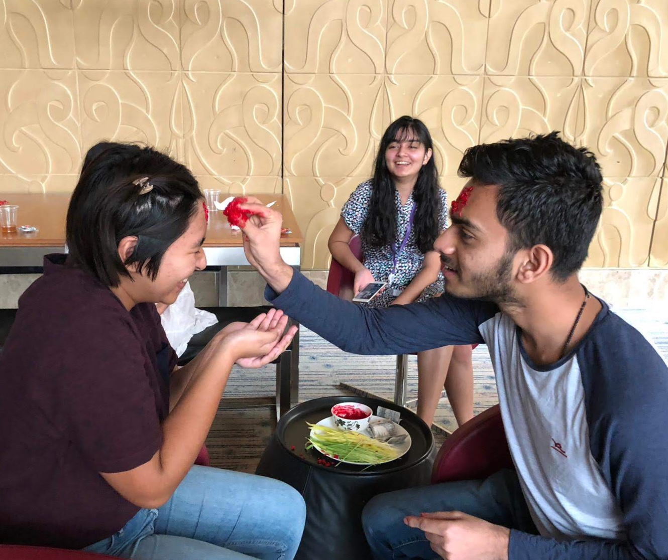 Bishal Sharma applies tika paint for Tanieshaa Shrestha in celebration of Daishan, a Nepali festival. These Nepali students gathered at EC to celebrate the festival together. Photo by Krishna Sharma