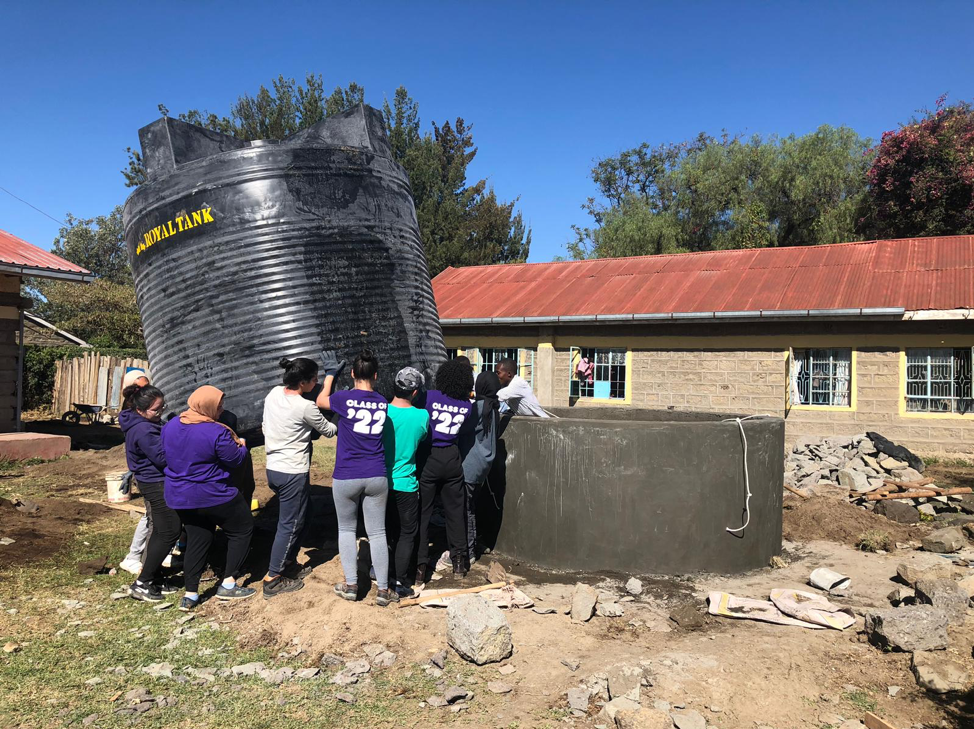 SLT team members place water tank into the foundation. Photo by Indee Thotawattage.