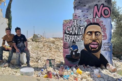 Artists Aziz Asmr and Anis Hamdoun pose next to a graffiti of George Floyd in Idlib, Syria, June 1, 2020. (Photo/ Mohamad Jamalo via REUTERS)